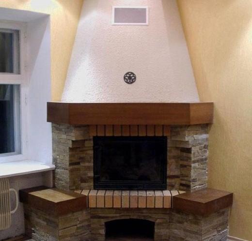 На снимке угловой камин с декоративной облицовкой