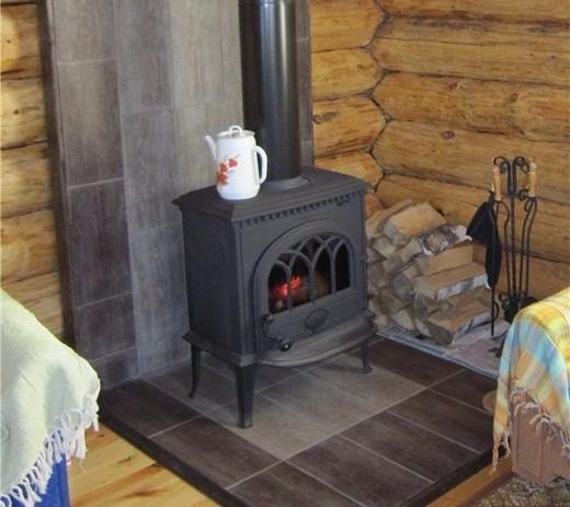На снимке представлена буржуйка с дымоходом, расположенная на кухне