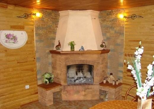 На фото пример углового дровяного камина (топочная камера и портал возведены посредством кирпичной кладки)