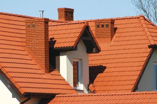 На фото вывод кирпичных дымоходов от каминов на крышу