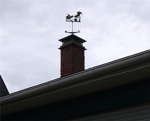 На фото дымоход оборудованный колпаком с флюгером, изображающим птиц