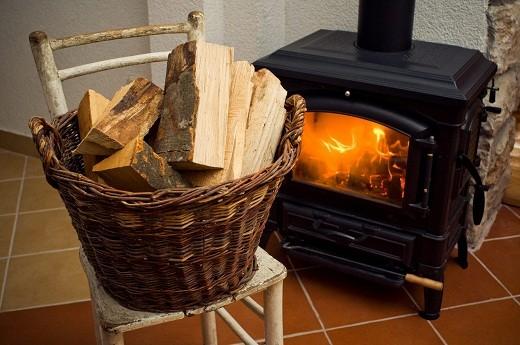 Плетеная корзинка, используемая в качестве поленницы для хранения дров, смотрится весьма колоритно